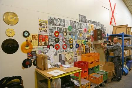 Calles vinylvägg med Calle framför främsta arbetsverktyget.
